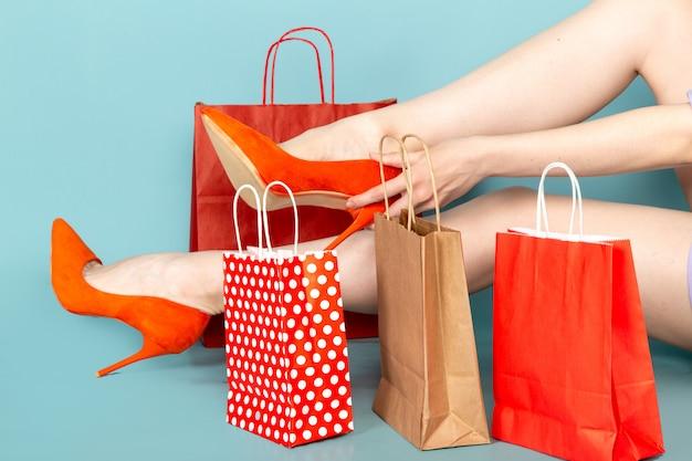 Eine attraktive frau der vorderansicht im blauen hemdkleid, das einkaufspakete hält und ihre schuhe auf blau trägt