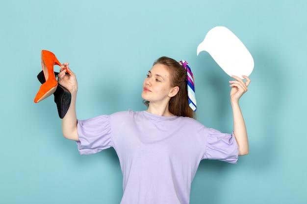 Eine attraktive frau der vorderansicht im blauen hemdkleid, das schwarze und orange schuhe auf blau hält