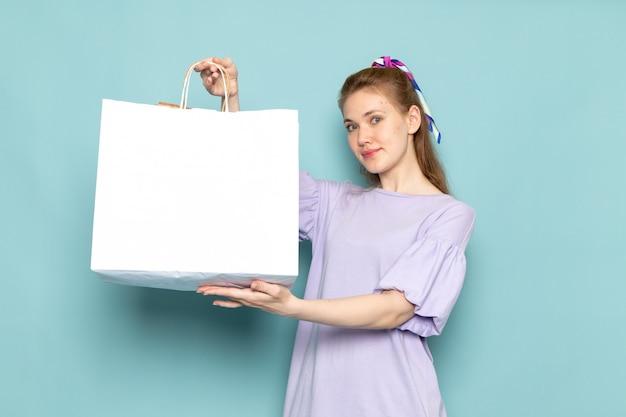 Eine attraktive frau der vorderansicht im blauen hemdkleid, das weißes einkaufspaket auf blau hält