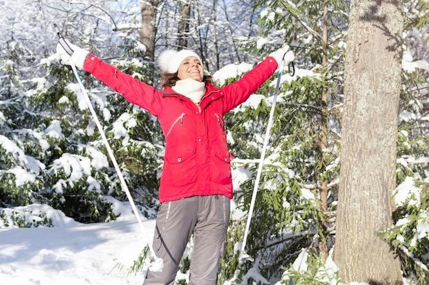 Eine attraktive frau geht durch den wald. sie fährt im park ski. gesunder lebensstil.