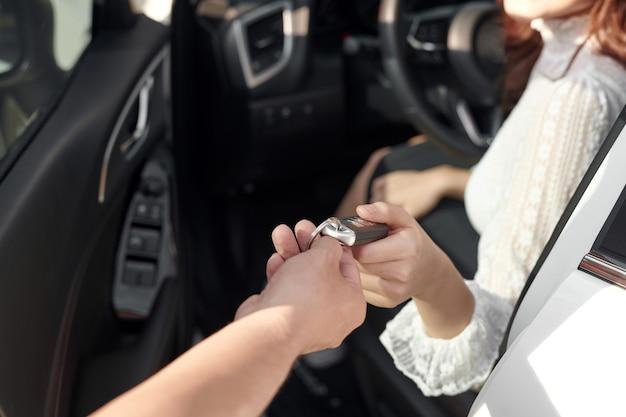 Eine attraktive frau in einem auto bekommt die autoschlüssel
