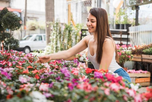 Eine attraktive glückliche junge frau, die um blühende pflanzen sich kümmert