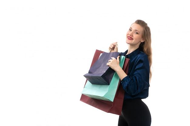 Eine attraktive junge dame der vorderansicht in der schwarzen hose der blauen bluse, die einkaufspakete hält, die glücklich auf der eleganten kleidung der weißen hintergrundmode lächeln