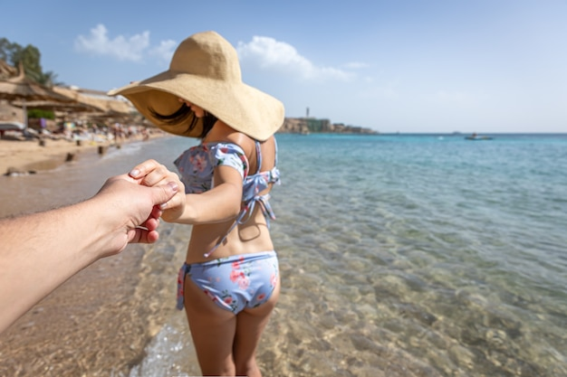 Eine attraktive junge frau am strand in einem badeanzug und einem großen hut geht mit einem mann an der hand.