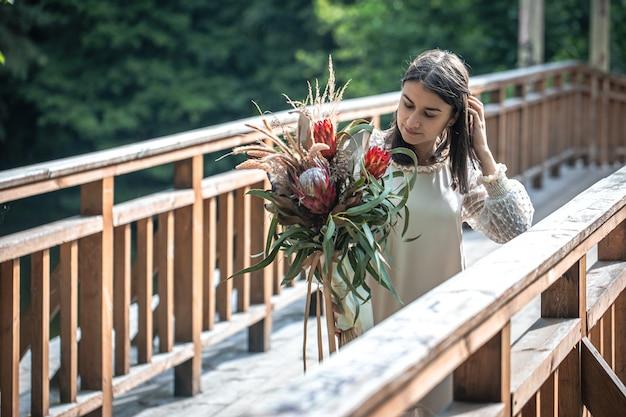 Eine attraktive junge frau auf einer holzbrücke steht mit einem strauß exotischer blumen.