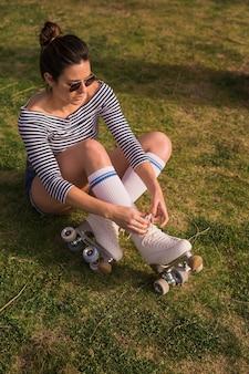 Eine attraktive junge frau, die auf dem grünen gras bindet die spitze des rollschuhs sitzt