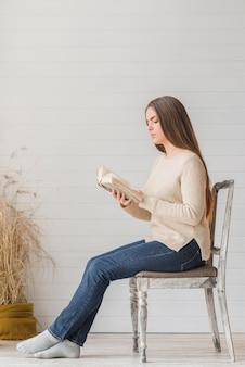 Eine attraktive junge frau, die auf holzstuhllesebuch gegen hölzerne wand sitzt