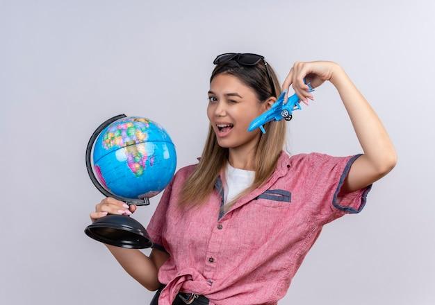 Eine attraktive junge frau, die ein rotes hemd in einer sonnenbrille trägt, die einen globus hält, während sie ein blaues spielzeugflugzeug fliegt und zwinkert