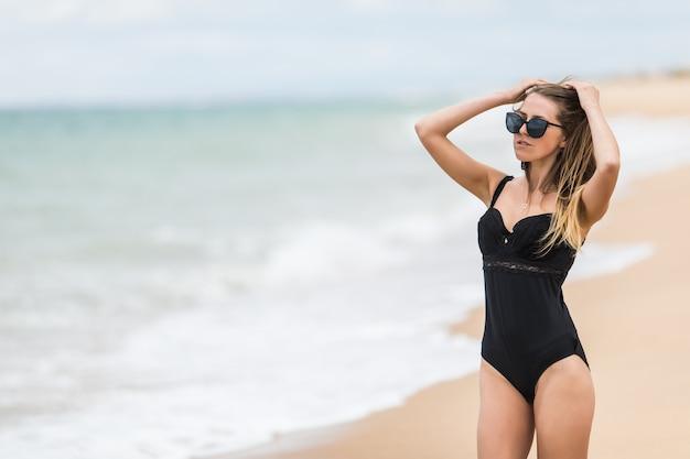 Eine attraktive junge frau, die einen schwarzen bikini trägt, sitzt mit dem ellbogen auf dem knie am strand