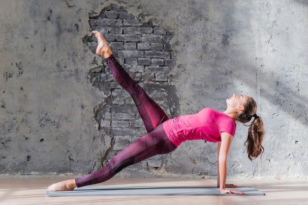 Eine attraktive junge frau, die ihr bein in der yogaklasse ausdehnt