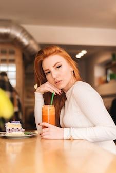 Eine attraktive junge frau, die im café mit köstlicher kuchenscheibe und smoothieglas auf holzoberfläche sitzt