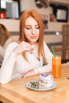 Eine attraktive junge frau, die im café mit köstlicher kuchenscheibe und smoothieglas sitzt