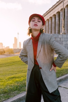 Eine attraktive junge frau im grauen mantel mit ihren händen auf der hüfte, die kamera betrachtet