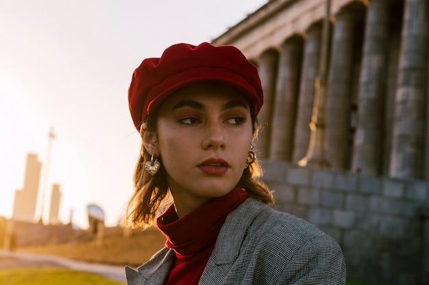 Eine attraktive junge frau in der roten kappe, die weg schaut