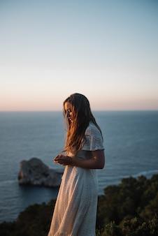 Eine attraktive junge frau mit einem schönen weißen kleid, das am abend am meer spazieren geht