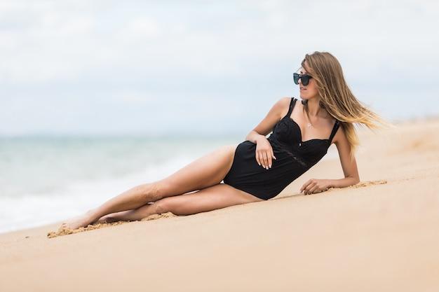 Eine attraktive sexy frau im badeanzug, die am strand liegt