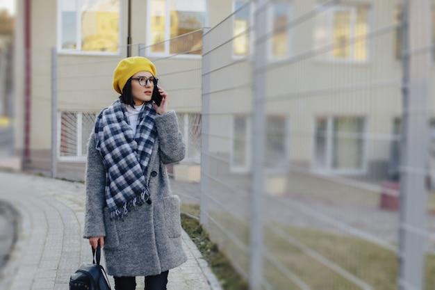 Eine attraktive tragende sonnenbrille des jungen mädchens in einem mantel, der hinunter die straße geht und am telefon und am lächeln spricht