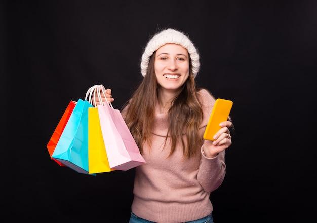 Eine aufgeregte junge frau über ihren online-einkauf. sie hält ein paar bunte taschen und ihr handy in der hand.