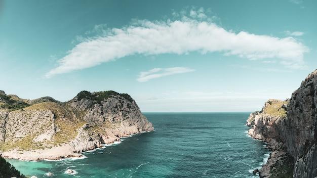 Eine augenbraue formte wolke über einem steilen klippengolf in mallorca, spanien.