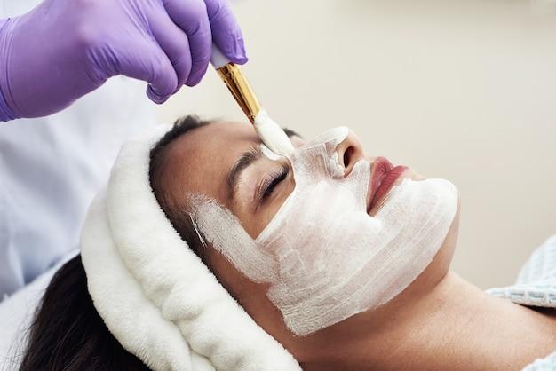 Eine ausgezeichnete kosmetikerin trägt mit einem pinsel eine weiße anti-aging-feuchtigkeitsmaske auf das gesicht auf