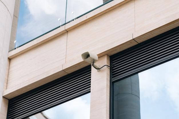 Eine außenüberwachungskamera an der wand eines bürogeschäftszentrums. das konzept, unternehmen vor rowdytum zu schützen