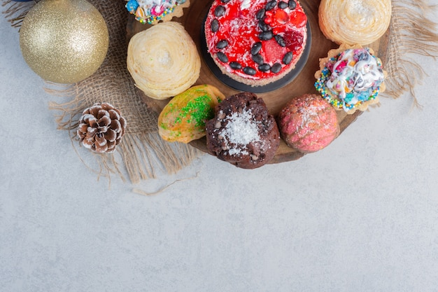 Eine auswahl an desserts auf einem holzbrett mit kugeln und tannenzapfen auf marmoroberfläche