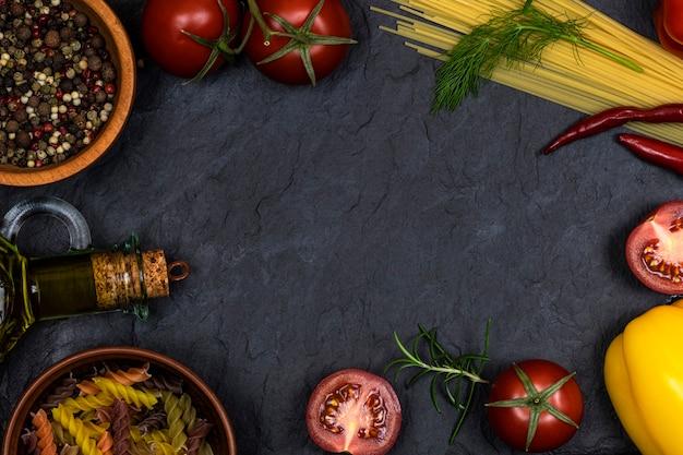 Eine auswahl an frischem gemüse, gewürzen, olivenöl in einer flasche, pasta auf schwarzem hintergrund mit platz für text.