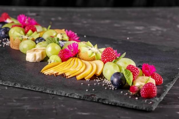Eine auswahl an saftigen leckeren früchten in einem leckeren gericht.