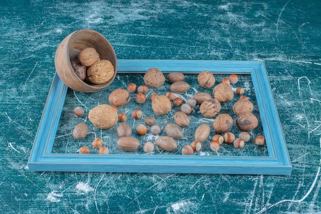Eine auswahl verschiedener nüsse in einem leeren rahmen auf blauem hintergrund. hochwertiges foto