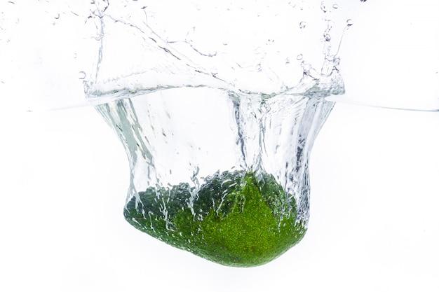Eine avocado, die ins wasser spritzt