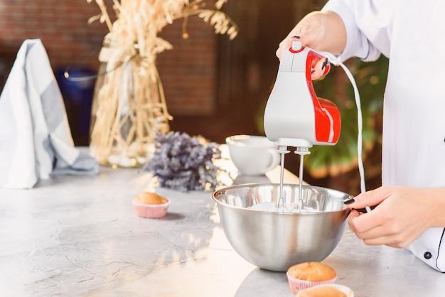 Eine bäckerin mischt eine frische sahne in einem tiefen teller mit einem roten küchenmixer. nahaufnahmefoto.