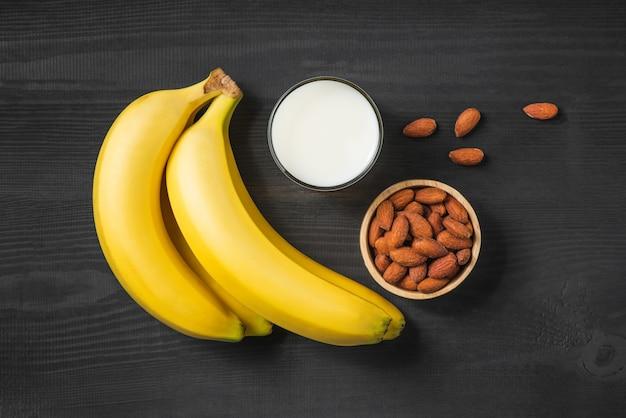 Eine banane mit mandeln und milch auf hölzernem hintergrund.