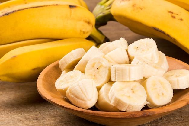Eine bananenbank und eine geschnittene banane in einem topf über einem tisch.