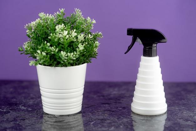 Eine barbier-spritzpistole neben einer topfblume befindet sich auf einer schwarzen marmorplatte mit einem schwarz-weißen kragen auf lila hintergrund