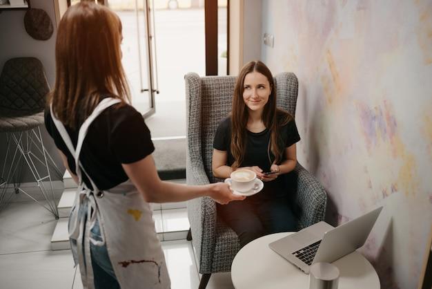 Eine barista-frau hält einem mädchen in einem café einen latte hin. eine frau mit langen haaren, die ferngesteuert an einem laptop arbeitet, hält soziale distanz und holt sich eine tasse kaffee in einem café.