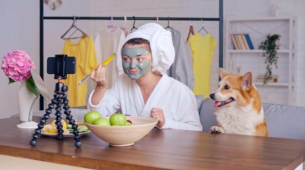 Eine beauty-bloggerin in einem weißen gewand mit einem weißen handtuch auf dem kopf trägt eine grüne feuchtigkeitsmaske auf ihr gesicht auf und bloggt über hautpflege und kosmetik. beauty-influencer der nächsten generation