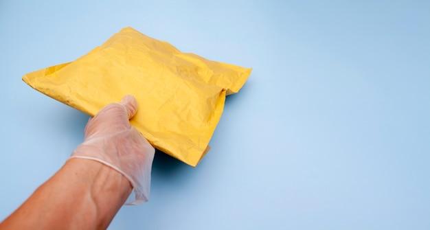 Eine behandschuhte hand hält ein bastelpaket. lieferung von waren während der quarantäne des coronavirus. speicherplatz kopieren