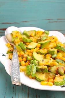 Eine beilage zucchini mit mais und käse