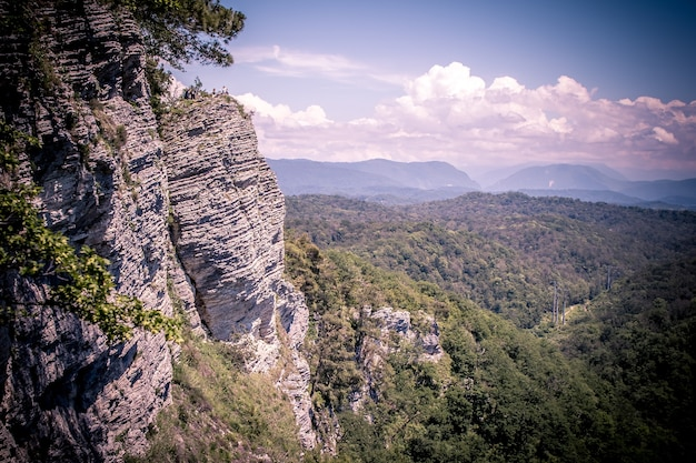 Eine bergkette unweit der stadt sotschi. hohe felsen und eine klippe darunter. adler felsen. grüner wald unten.