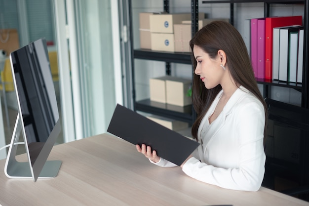 Eine berufstätige frau in der weißen klage arbeitet im büro.