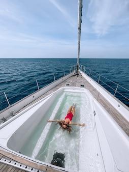 Eine bezaubernde schlanke frau schwimmt im pool auf der yacht