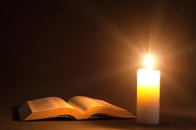 Eine bibel auf dem tisch im licht einer kerze