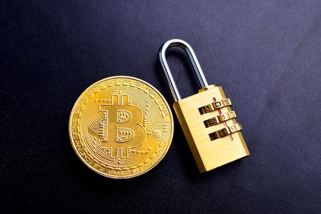 Eine bitcoin-kryptowährung mit sperre auf schwarzem texturhintergrund mit textraum, bitcoin-betrugspräventionskonzept