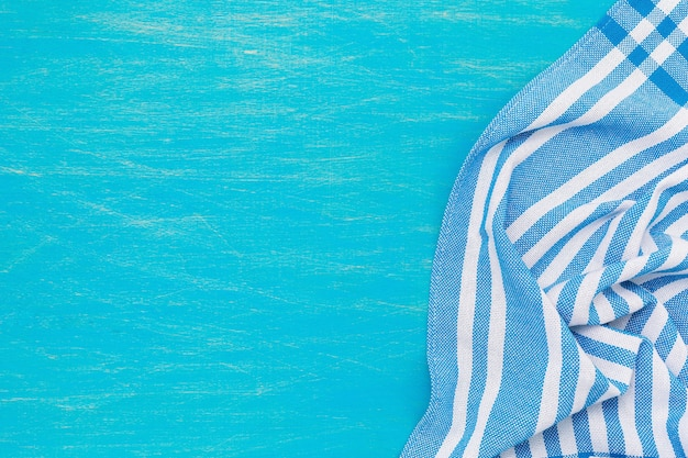 Eine blau-weiße serviette auf der rechten seite eines hellblauen holztisches, ansicht von oben