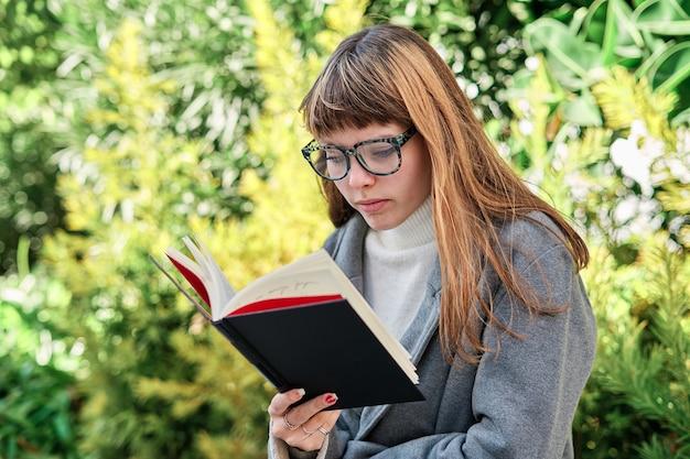 Eine blauäugige kaukasische blonde junge frau mit brille, die ein buch im park liest