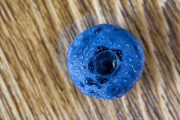 Eine blaubeerbeere mit wassertropfen auf einem holztisch, nahaufnahmefoto, draufsicht