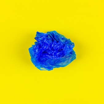 Eine blaue plastiktasche auf gelbem hintergrund, draufsicht.