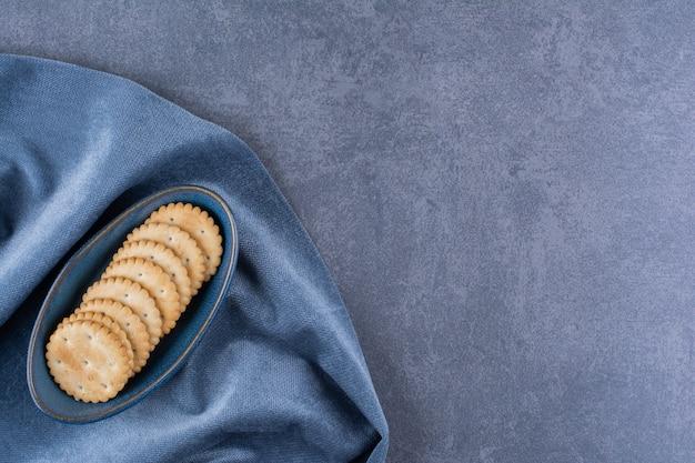 Eine blaue schüssel butterkekse für tee auf tischdecke.