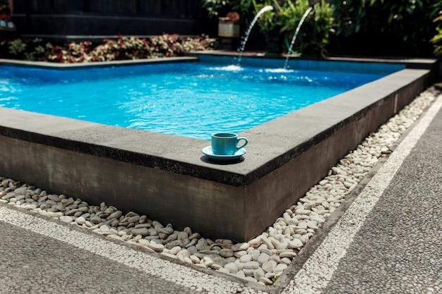 Eine blaue tasse kaffee steht an der ecke eines tropischen pools mit weißem stein bedeckt, komfortable ferien in asien