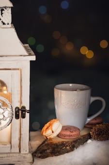 Eine blaue tasse mit einem heißen getränk und keksen im schnee. winterurlaub konzept.